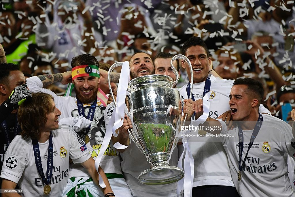 Real Madrid's French forward Karim Benzema (C) lifts the trophy after Real Madrid won the UEFA Champions League final football match between Real Madrid and Atletico Madrid at San Siro Stadium in Milan, on May 28, 2016. / AFP / PIERRE