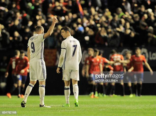 Real Madrid's French forward Karim Benzema speaks with teammate Portuguese forward Cristiano Ronaldo after a goal by Osasuna during the Spanish...