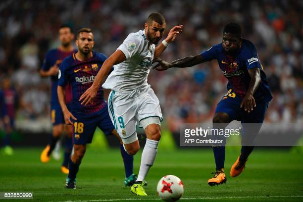 Real Madrid's French forward Karim Benzema vies with Barcelona's French defender Samuel Umtiti during the second leg of the Spanish Supercup football...