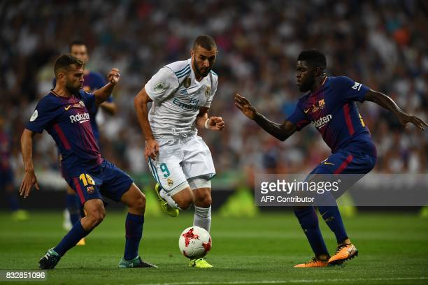 Real Madrid's French forward Karim Benzema vies with Barcelona's French defender Samuel Umtiti and Barcelona's defender Jordi Alba during the second...