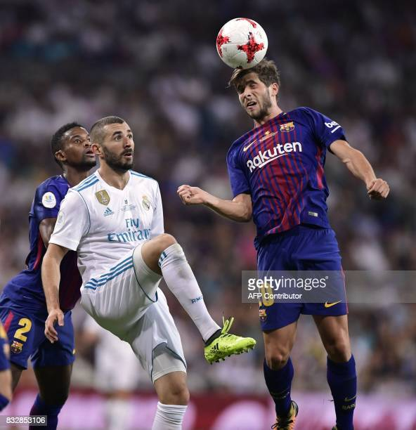 Real Madrid's French forward Karim Benzema vies with Barcelona's Portuguese defender Nelson Semedo and Barcelona's midfielder Sergi Roberto during...