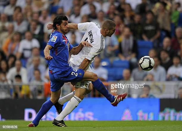 Real Madrid's French forward Karim Benzema vies with Getafe's defender Miguel Torres during their Liga football match at Santiago Bernabeu stadium in...