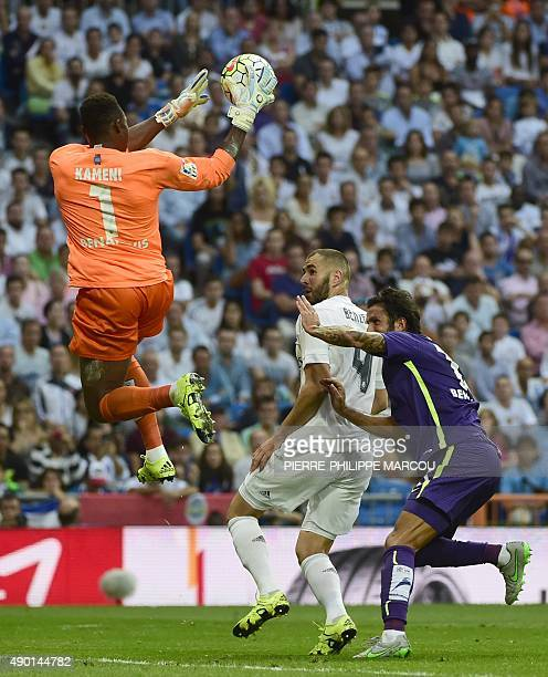 Real Madrid's French forward Karim Benzema vies with Malaga's Cameroonian goalkeeper Idriss Kameni and Malaga's defender Miguel Torres during the...