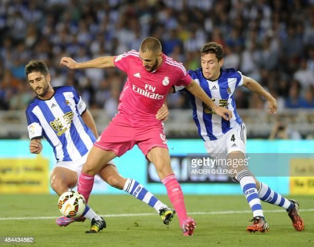 Real Madrid's French forward Karim Benzema vies with Real Sociedad's midfielder Markel Bergara and midfielder Gorka Elustondo during the Spanish...