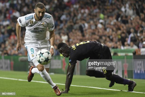 Real Madrid's French forward Karim Benzema vies with Tottenham Hotspur's Colombian defender Davinson Sanchez during the UEFA Champions League group H...