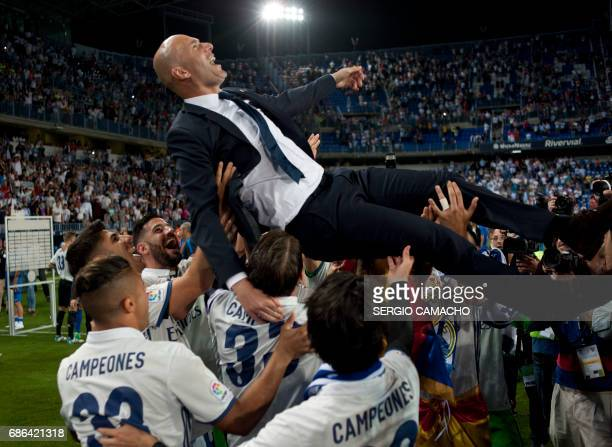 Real Madrid's French head coach Zinedine Zidane is tossed by players at the end of the Spanish league football match Malaga CF vs Real Madrid at La...