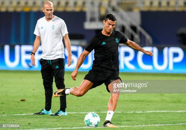 TOPSHOT Real Madrid's French head coach Zinedine Zidane looks on as Real Madrid's forward Cristiano Ronaldo shoots the ball during a training session...