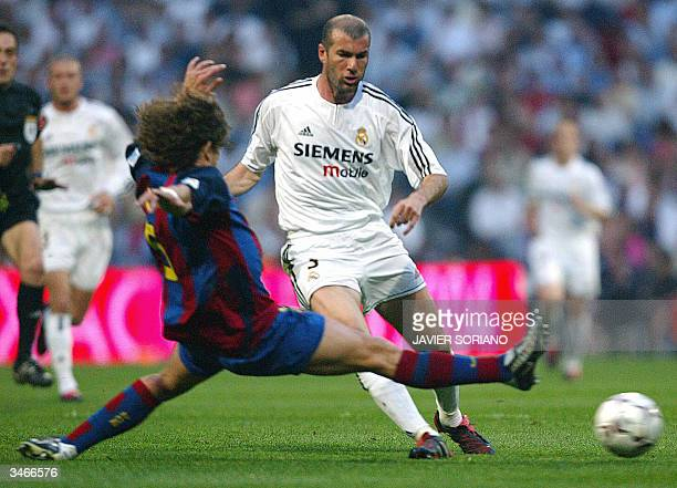 Real Madrid's French Zinedine Zidane vies with Barcelona's Carles Puyol during their Spanish Premier League football match at Santiago Bernabeu...