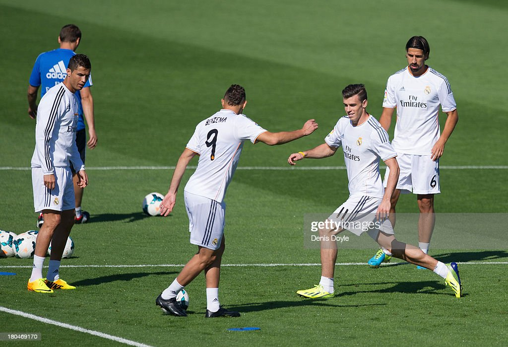 Real Madrid's <a gi-track='captionPersonalityLinkClicked' href=/galleries/search?phrase=Gareth+Bale&family=editorial&specificpeople=609290 ng-click='$event.stopPropagation()'>Gareth Bale</a> (2.R) challenges <a gi-track='captionPersonalityLinkClicked' href=/galleries/search?phrase=Karim+Benzema&family=editorial&specificpeople=796089 ng-click='$event.stopPropagation()'>Karim Benzema</a> (#9) while <a gi-track='captionPersonalityLinkClicked' href=/galleries/search?phrase=Cristiano+Ronaldo+-+Soccer+Player&family=editorial&specificpeople=162689 ng-click='$event.stopPropagation()'>Cristiano Ronaldo</a> (L) and <a gi-track='captionPersonalityLinkClicked' href=/galleries/search?phrase=Sami+Khedira&family=editorial&specificpeople=2513712 ng-click='$event.stopPropagation()'>Sami Khedira</a> (#6) look on during a team training session on September 13, 2013 in Madrid, Spain.