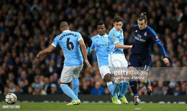 Real Madrid's Gareth Bale is stopped in his tracks by Manchester City's Fernando and Jesus Navas