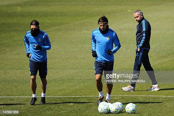 Real Madrid's German midfielder Mesut Ozil and Real Madrid's German midfielder Sami Khedira run next to Real Madrid's Portuguese coach Jose Mourinho...