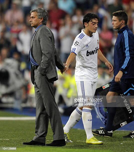 Real Madrid's German midfielder Mesut Ozil is congratulated by his Portuguese coach Jose Mourinho during their Champions league group G football...