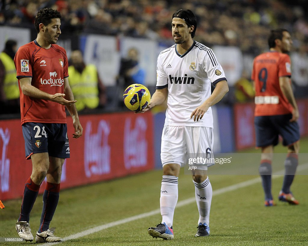 Real Madrid's German midfielder Sami Khedira (R) reacts near Osasuna's defender Damia Abella during the Spanish league football match CA Osasuna vs Real Madrid CF at the Reyno de Navarra stadium in Pamplona on January 12, 2013.