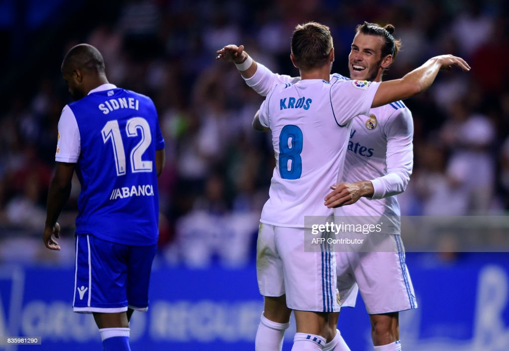 Real Madrid's German midfielder Toni Kroos (C) celebrates with teammate Welsh forward Gareth Bale next to Deportivo La Coruna's Brazilian defender Sidnei after scoring during the Spanish league footbal match RC Deportivo de la Coruna vs Real Madrid CF at the Municipal de Riazor stadium in La Coruna on August 20, 2017. /