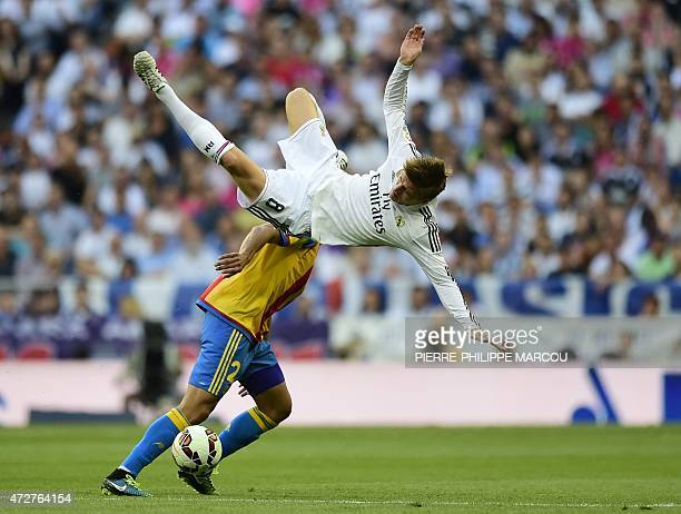 Real Madrid's German midfielder Toni Kroos falls as he vies with Valencia's Portuguese midfielder Andre Gomes during the Spanish league football...