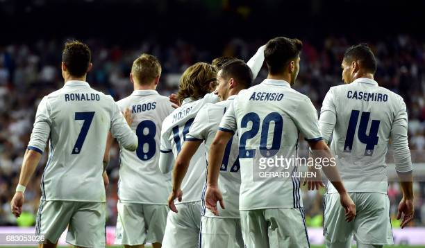 CORRECTION Real Madrid's German midfielder Toni Kroos is congratulated by his teammates after scoring during the Spanish league football match Real...