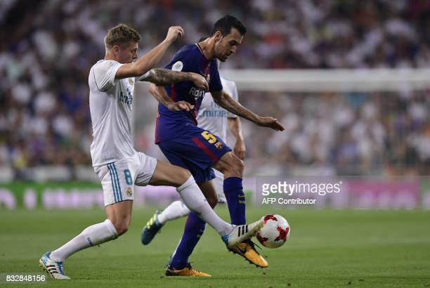 Real Madrid's German midfielder Toni Kroos vies with Barcelona's midfielder Sergio Busquets during the second leg of the Spanish Supercup football...