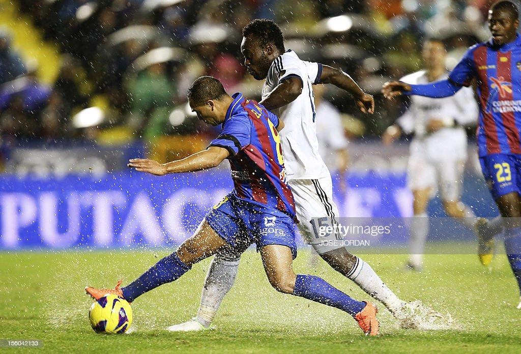 Real Madrid's Ghanaian midfielder Michael Essien (R) vies with Levante's Greek defender Nikolaos Karabelas (L) during the Spanish league football match Levante UD vs Real Madrid at Ciutat de Valencia in Valencia on November 11, 2012.