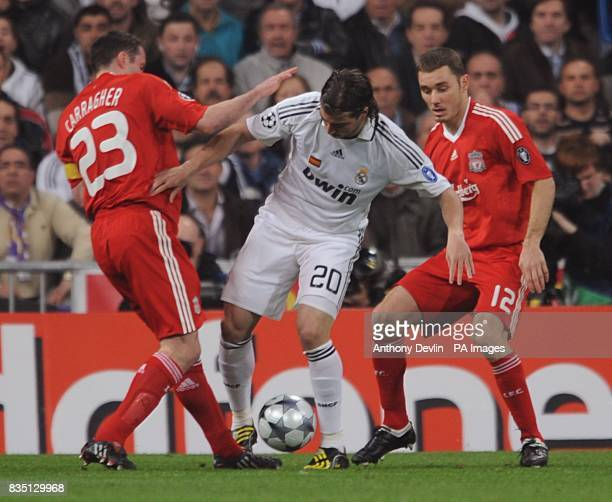 Real Madrid's Gonzalez Raul battles for the ball with Liverpool's Jamie Carragher and Fabio Aurelio