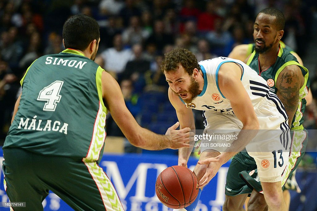 Real Madrid's guard Sergio Rodriguez (C) vies with Unicaja's Croatian forward Krunoslav Simon (L) and Unicaja's US guard Earl Calloway during the Euroleague basketball match Real Madrid vs Unicaja Malaga at the Palacio de los Deportes in Madrid on March 15, 2013.