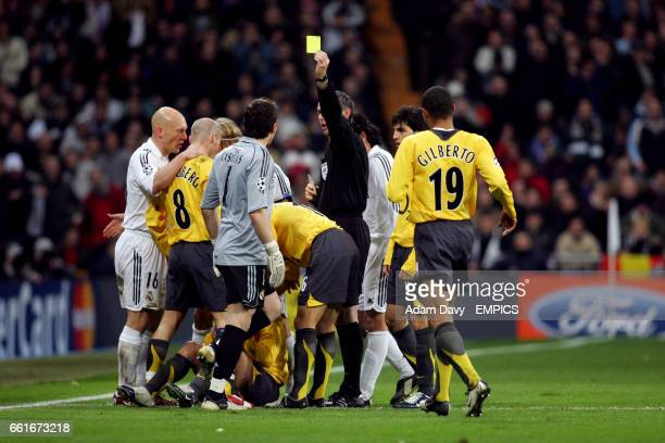 Real Madrid's Iker Casillas is booked by referee Stefano Farina after clashing with Arsenal's Jose Antonio Reyes