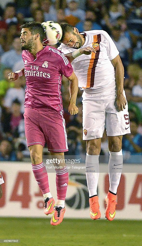 Real Madrid's Isco and AS Roma's Leandro Castan, right, vie for a header in the Guinness International Champions Cup at the Cotton Bowl in Dallas on Tuesday, July 29, 2014.