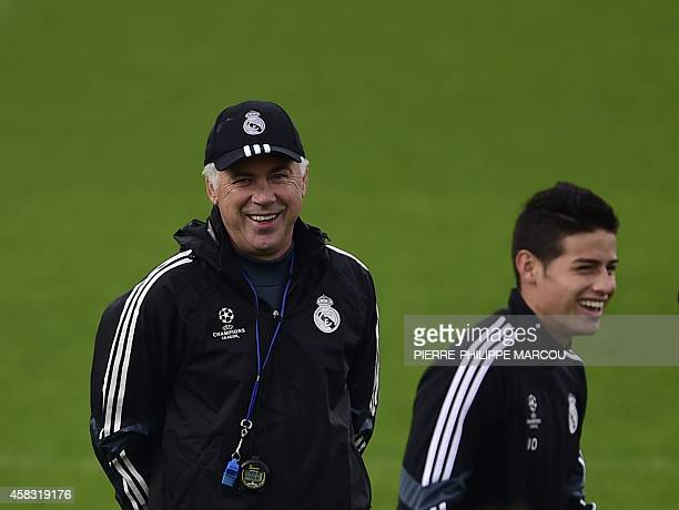 Real Madrid's Italian coach Carlo Ancelotti and Real Madrid's Colombian midfielder James Rodriguez take part in training session at the Valdebebas...