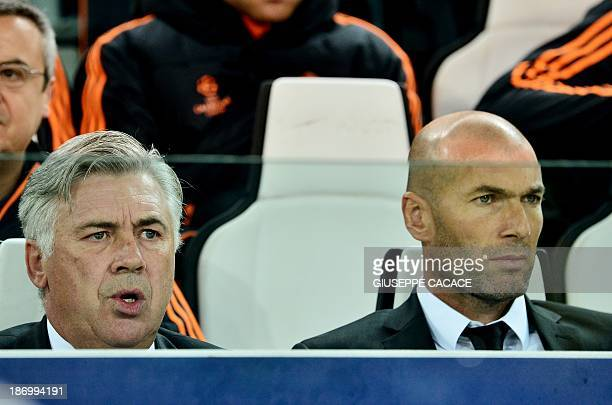Real Madrid's Italian coach Carlo Ancelotti and Real Madrid's French assistant manager Zinedine Zidane watch on November 5 2013 their team play...
