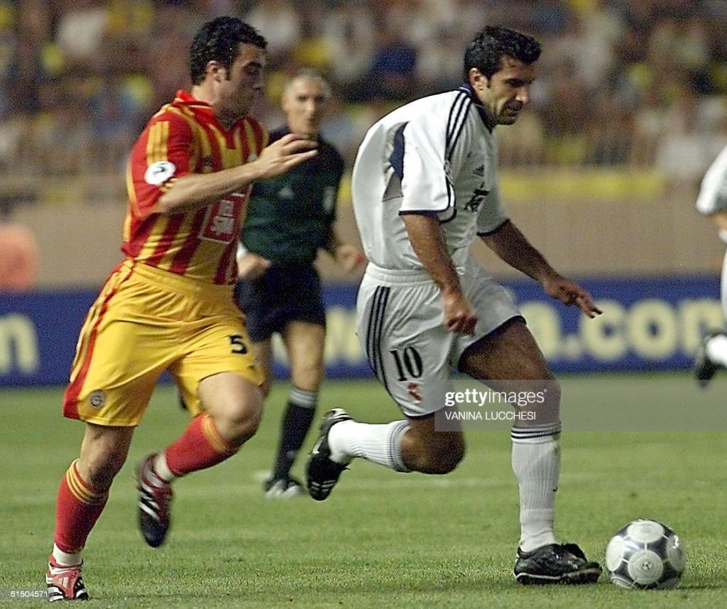 Real Madrid s Luis Figo R escapes with the ball