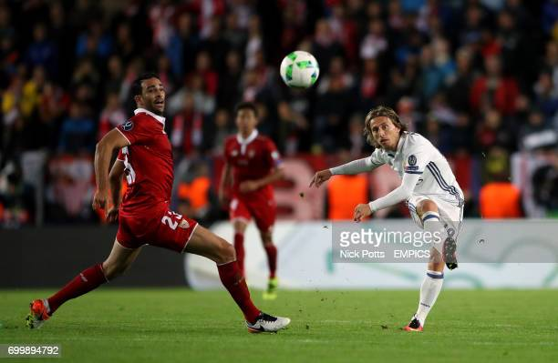 Real Madrid's Luka Modric crosses under pressure from Sevilla's Adil Rami
