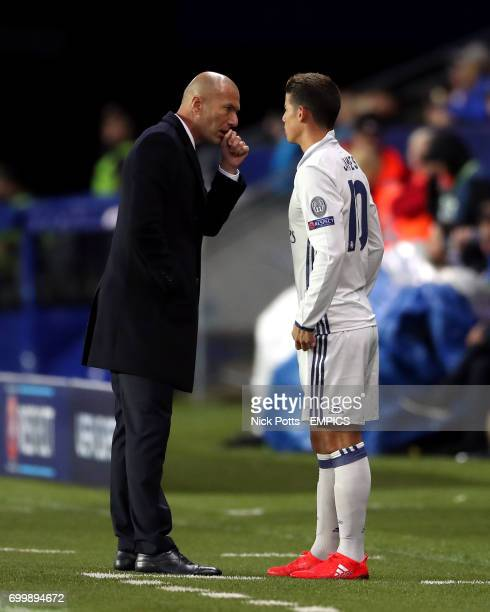 Real Madrid's manager Zinedine Zidane speaks with James Rodriguez as he comes on