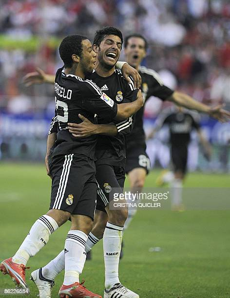 Real Madrid's Marcelo Vieira celebrates after scoring a goal against Sevilla with Miguel Torres during their Spanish league football match at Sanchez...