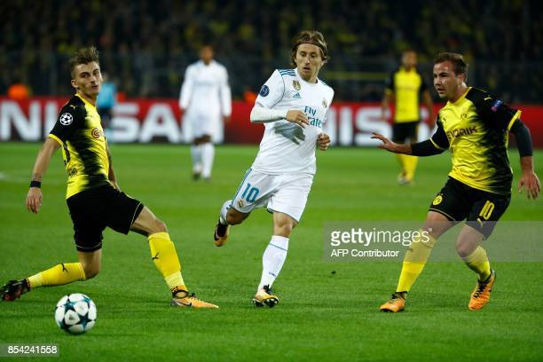 Real Madrid's midfielder from Croatia Luka Modric vies for the ball with Dortmund's German midfielder Mario Goetze and Dortmund's German forward...