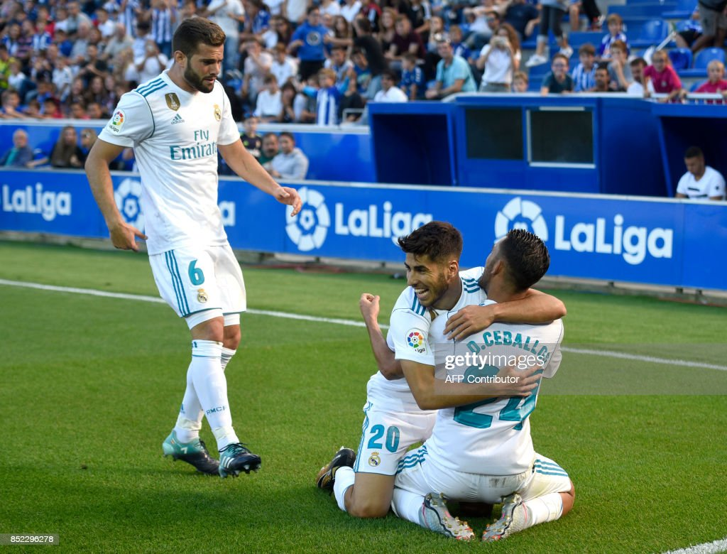 Real Madrid's midfielder from Spain Daniel Ceballos (R) celebrates his team's second goal with teammates Real Madrid's midfielder from Spain Marco Asensio (C) and Real Madrid's defender from Spain Nacho Fernandez during the Spanish league football match Deportivo Alaves vs Real Madrid CF at the Mendizorroza stadium in Vitoria on September 23, 2017. /