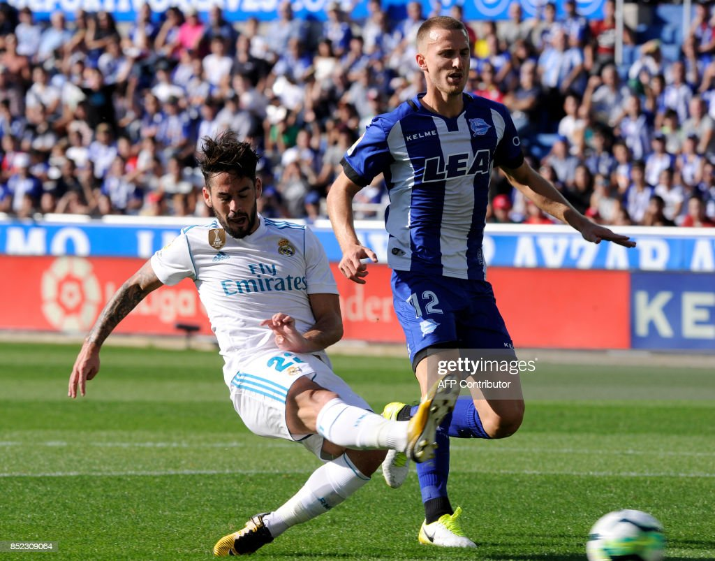 Real Madrid's midfielder from Spain Isco (L) vies with Alaves' defender from Brazil Rodrigo Ely during the Spanish league football match Deportivo Alaves vs Real Madrid CF at the Mendizorroza stadium in Vitoria on September 23, 2017. /