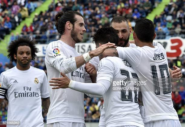 Real Madrid's midfielder Isco is congratulated by Real Madrid's Welsh forward Gareth Bale and Real Madrid's French forward Karim Benzema after...