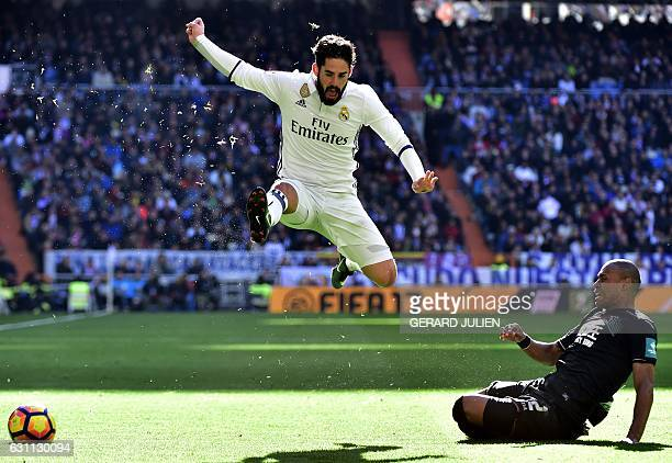 TOPSHOT Real Madrid's midfielder Isco jumps to avoid Granada's Brazilian defender Gabriel Silva during the Spanish league football match Real Madrid...