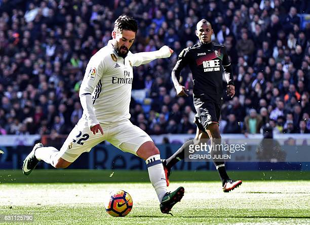 Real Madrid's midfielder Isco kicks the ball to score during the Spanish league football match Real Madrid CF vs Granada FC at the Santiago Bernabeu...
