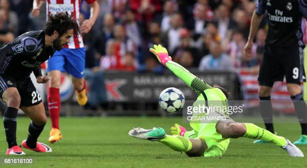 Real Madrid's midfielder Isco looks at Atletico Madrid's Slovenian goalkeeper Jan Oblak after shooting to score a goal during the UEFA Champions...