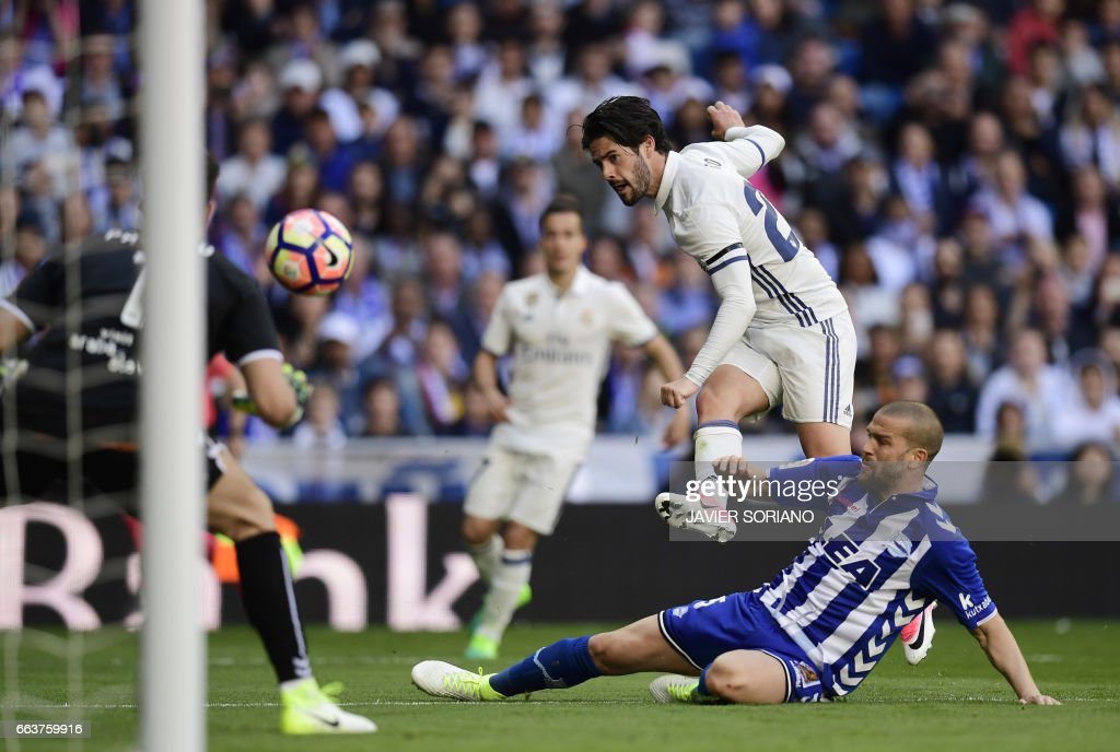 Real Madrid's midfielder Isco (top) shoots to score a goal beside Deportivo Alaves' Brazilian defender Rodrigo Ely (R) and Deportivo Alaves' goalkeeper Fernando Pacheco (L) during the Spanish league football match Real Madrid CF vs Deportivo Alaves at the Santiago Bernabeu stadium in Madrid on April 2, 2017. /