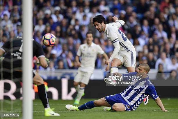 Real Madrid's midfielder Isco shoots to score a goal beside Deportivo Alaves' Brazilian defender Rodrigo Ely and Deportivo Alaves' goalkeeper...