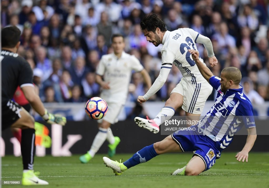 Real Madrid's midfielder Isco (C) shoots to score a goal beside Deportivo Alaves' Brazilian defender Rodrigo Ely (R) and Deportivo Alaves' goalkeeper Fernando Pacheco (L) during the Spanish league football match Real Madrid CF vs Deportivo Alaves at the Santiago Bernabeu stadium in Madrid on April 2, 2017. /