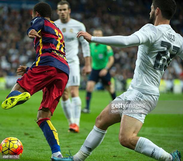 Real Madrid's midfielder Isco tackles Barcelona's Brazilian forward Neymar during the Spanish league 'Clasico' football match Real Madrid CF vs FC...