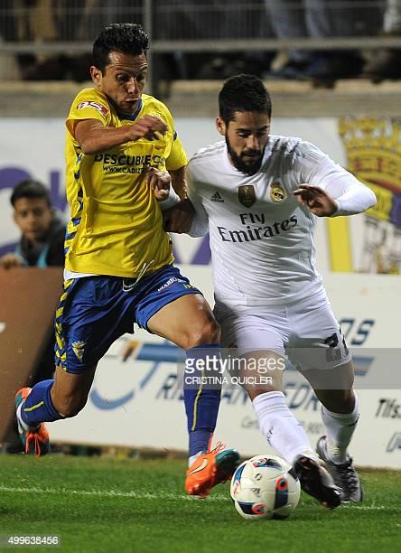 Real Madrid's midfielder Isco vies with Cadiz's midfielder Mantecon during the Spanish Copa del Rey football match Cadiz CF vs Real Madrid at the...