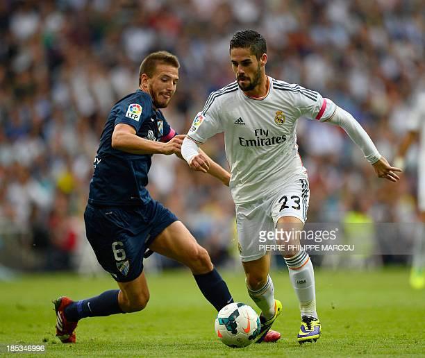 Real Madrid's midfielder Isco vies with Malaga's midfielder Ignacio Camacho during the Spanish league football match Real Madrid vs Malaga on October...