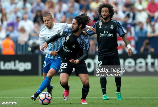 Real Madrid's midfielder Isco vies with Malaga's midfielder Sergio Gontan during the Spanish league football match Malaga CF vs Real Madrid CF at La...