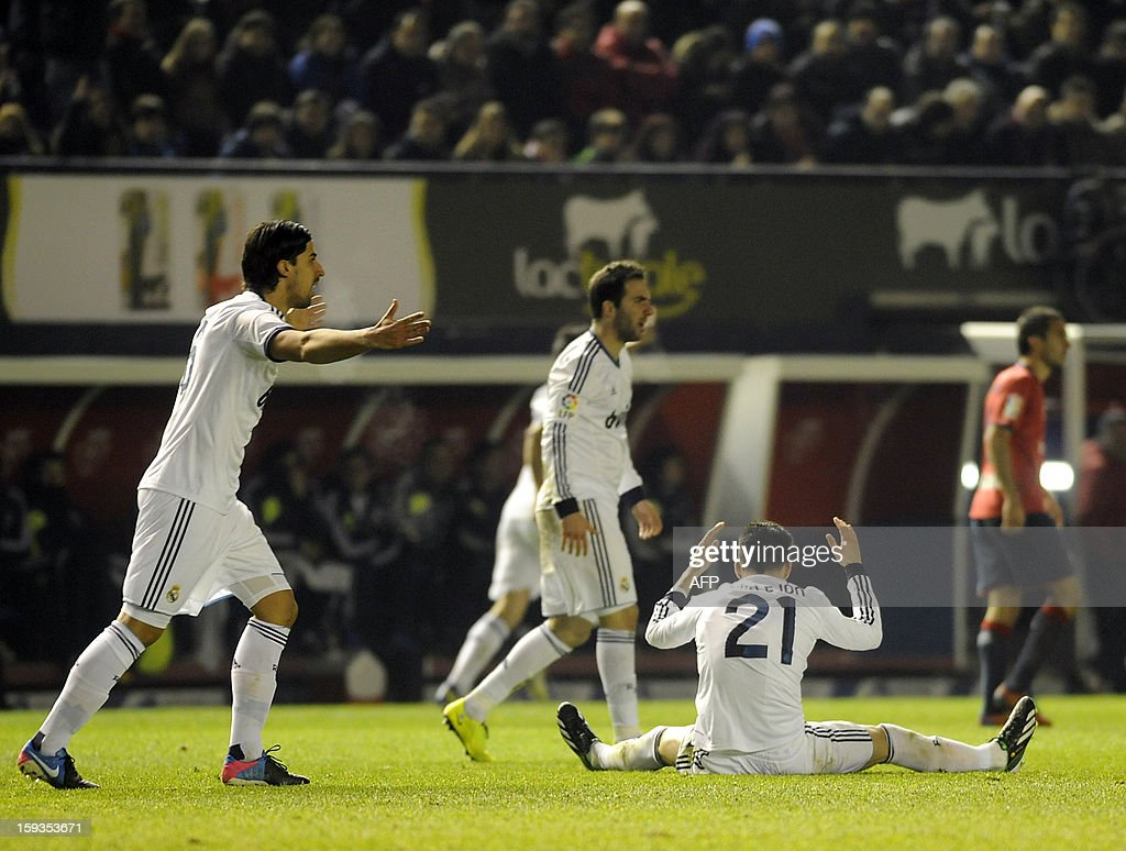 Real Madrid's midfielder Jose Maria Callejon (down) and German midfielder Sami Khedira (L) react during the Spanish league football match CA Osasuna vs Real Madrid CF at the Reyno de Navarra stadium in Pamplona on January 12, 2013.