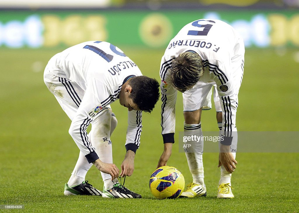 Real Madrid's midfielder Jose Maria Callejon (L) and Portuguese defender Fabio Coentrao (R) talk during the Spanish league football match CA Osasuna vs Real Madrid CF at the Reyno de Navarra stadium in Pamplona on January 12, 2013. The match ended in a draw 0-0.