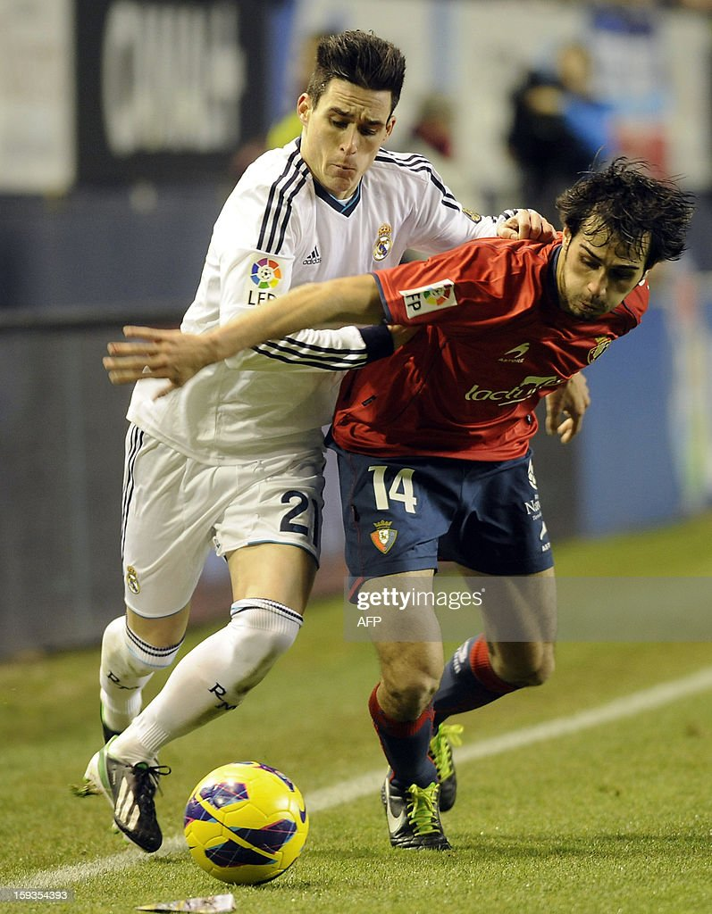 Real Madrid's midfielder Jose Maria Callejon (L) vies with Osasuna's defender Alejandro Arribas (R) during the Spanish league football match CA Osasuna vs Real Madrid CF at the Reyno de Navarra stadium in Pamplona on January 12, 2013. The match ended in a draw 0-0.