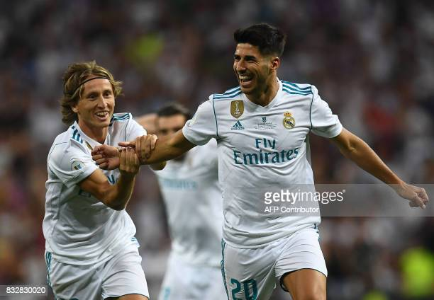 Real Madrid's midfielder Marco Asensio celebrates with Real Madrid's Croatian midfielder Luka Modric after scoring the opener during the second leg...